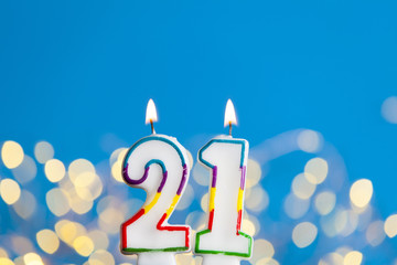 Number 21 Birthday Celebration Candle Against A Bright Lights And Blue Background