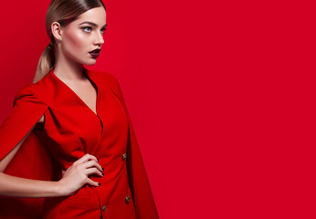 In the studio on a gray background is a beautiful young thin fashionable girl in a red long jacket with gold buttons and bright make-up with a smooth hairdo.