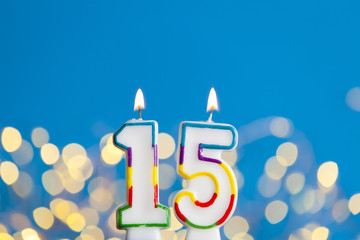 Number 15 birthday celebration candle against a bright lights and blue background