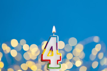 Number 4 birthday celebration candle against a bright lights and blue background