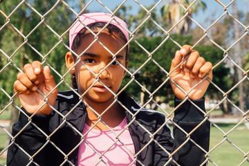 Portrait of schoolgirl holding wire fence on school sports field