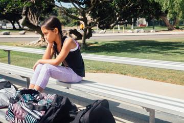 Schoolgirl soccer player alone on bench on school sports field