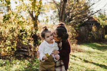 Girl hugging younger sister, in rural setting