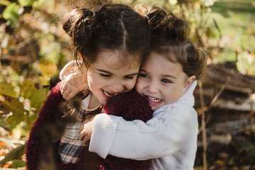 Two young sisters hugging, in rural setting