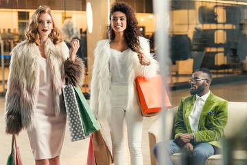 stylish young multiethnic women with shopping bags walking and african american man sitting behind in mall