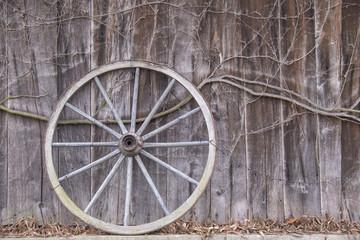 Altes Wagenrad lehnt an einer Scheunenwand