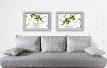 Two wooden frames with floral posters over modern couch near white bricks wall, interior decor mockup