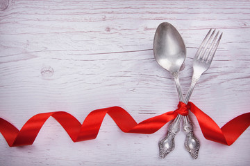 Vintage spoon and fork with a red tape for Valentine's day on a wooden table.