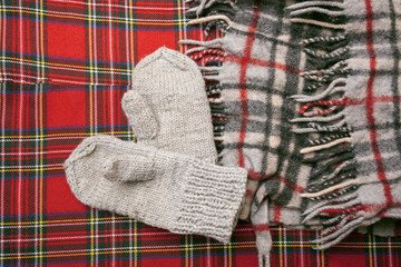 Warm woolen scarf and mittens on a red background