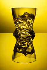 Cocktail whiskey a glass with pieces ice of party reflection a concept of hourglasses on yellow background.