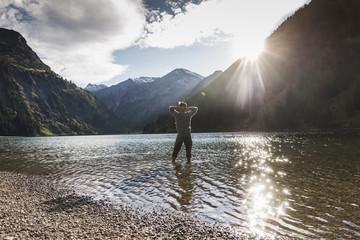 Austria, Tyrol, hiker refreshing in mountain lake
