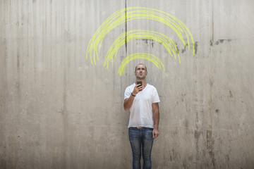 Man holding cell phone with yellow chalk wifi sign above his head