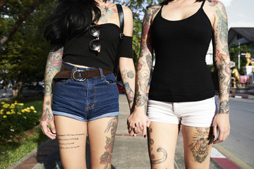 Tattooed lesbian couple holding hands in the street in summer