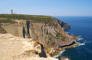 The big cliffs and a lighthouse on the cape Espichel. Portugal
