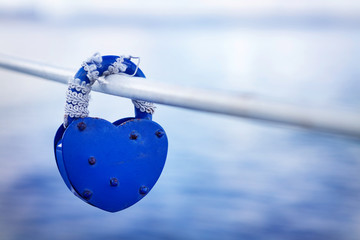 padlock in the shape of a heart on a bridge railing above the river