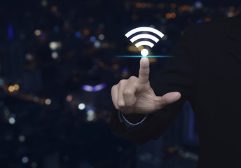 Businessman pointing to wi-fi button over blur colorful night light city tower, Technology and internet concept