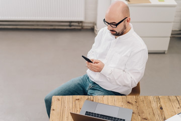 High-angle view of man using mobile phone at desk
