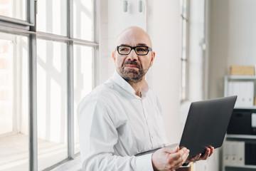 Businessman standing holding an open laptop