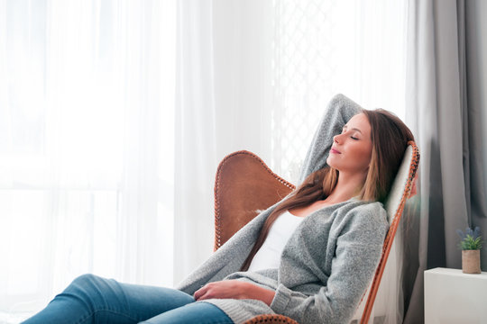Woman at home sitting on modern chair near window relaxing in living room