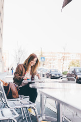 young woman sitting outdoor bar having coffee smiling - happiness, positive emotions, attitude concept