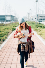 Young woman walking in the city playing ukulele - busker, musician, composer concept