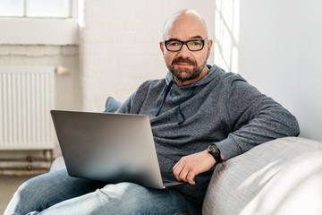 Portrait of a middle-aged man holding a laptop