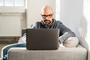 Man relaxing at home working on a laptop