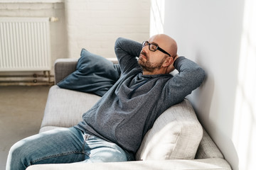 Middle-aged man relaxing on the couch indoors