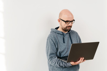 Casual man standing using a handheld laptop