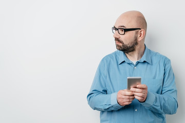 Man holding a mobile phone looking to the side