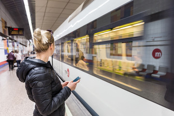 Young casual woman with a cell phone in her hand waiting on the platform of a metro station for metro to arrive. Public transport.