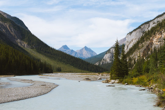 Scenic remote wide valley with river and forest in Rocky Mountains in Canada on cloudy day