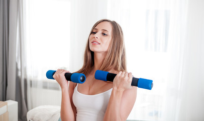 Sporty young woman exercising at home with dumbbells
