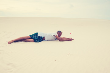 Exhausted man, lost in the desert, crawls on the sand