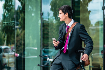 Young corporate employee holding a mobile phone while waiting outdoors in a modern European city