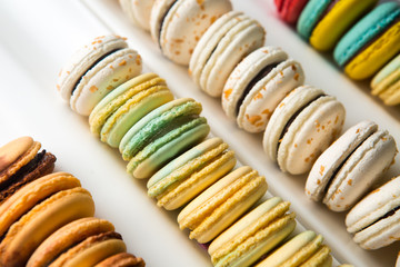 Set of different french cookies macaroons in a white box. Closeup. Coffee, chocolate, vanilla, lemon, raspberry, strawberry, pistachio, violet, rose, orange tastes macaroons