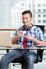 Young indonesian professional working in city office on notebook and having coffee