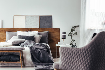 Gray armchair facing white bed
