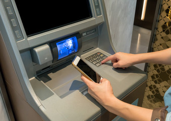 Asian woman looking at mobile phone display while pressing digit buttons on ATM machine.