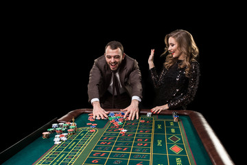 Man with woman playing roulette at the casino. Addiction to the