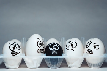 Faces on chicken eggs in the form of facial expressions, reflecting emotions. The concept of racism, misunderstanding, a barrier in relations, denial of society. Barriers between people, prejudice.