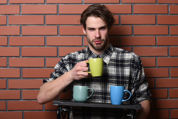 handsome guy holding cups on brick wall background