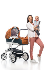 happy mother with infant baby in hands looking at camera with baby carriage behind isolated on white