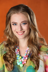 Portrait of gorgeous pretty slender blonde girl-model in a bright silk dress. Happy young woman smiling.