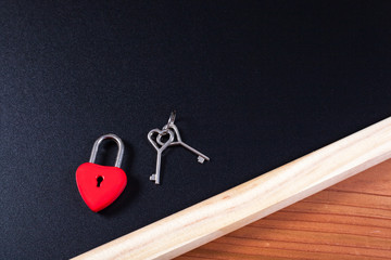 A locked red heart shaped lock with a key stuck on background.