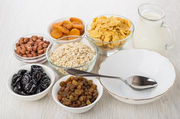 Empty bowl, spoon, milk, ingredients for preparation muesli on table