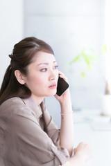 窓際で通話をする若い女性