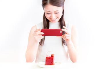 スマートフォンでケーキを撮影する若い女性