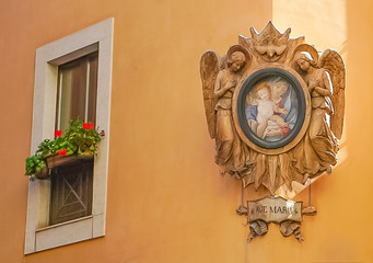 A Carved Angel and Ave Maria Frame with frescoe of Mary and Jesus on the side of building and a window with flowers on side street in Rome, Italy