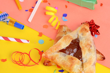 Purim background with party costume and hamantaschen cookies.